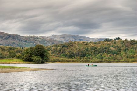Two people canoeing on Rydal Water in the English Lake District under an overcast sky Stock Photo - 1849701