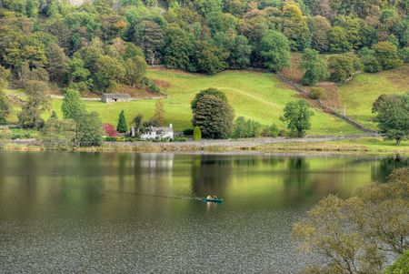 Two people canoeing on Rydal Water in the English Lake District under an overcast sky