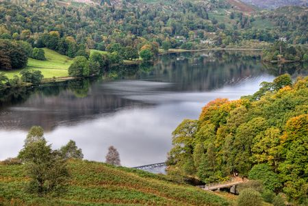 A view of Grasmere in the English Lake District, with early Autumn colours in the foreground trees which are lit by the sun. Two people can be seen crossing a wooden bridge in front of a wier Stock Photo
