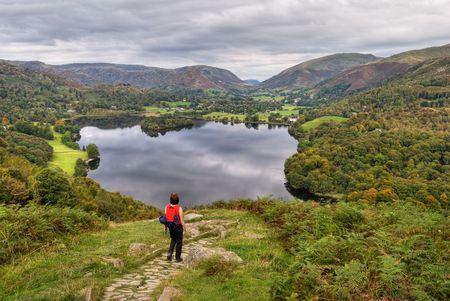 W związku z Grasmere w angielskiej Lake District, z wczesną jesienią kolory w planie drzew, które są oświetlone przez niedziela Dwie osoby mogą być postrzegane skrzyźowaniu drewnianego mostu przed wier