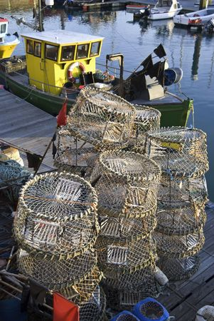 Lobster pots and a small fishing boat at Brighton Marina, East Sussex, England, UK