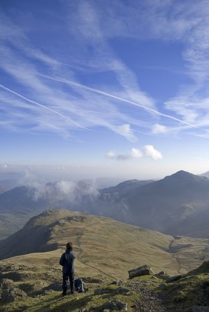 A female hiker looking down the Band from near the summit of Bowfell in the English lake District