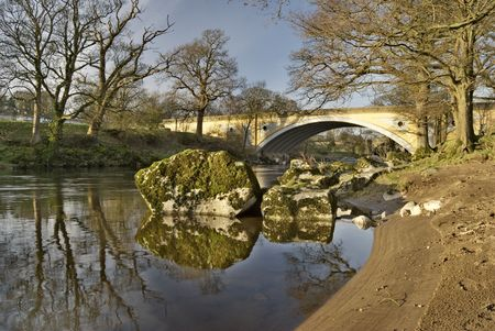 The sandy bank of the river Lune with the modern road bridge at Kirkby Lonsdale, Cumbria, England