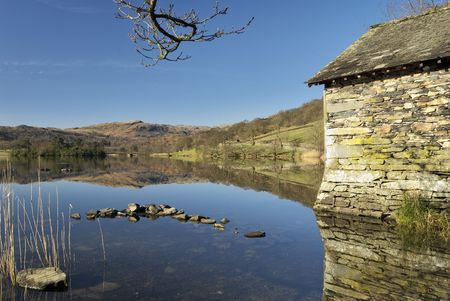 boathouse: A boathouse reflected in the still waters of Rydal Water in the English Lake District. Stock Photo