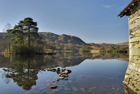 A boathouse reflected in the still waters of Rydal Water in the English Lake District. Stock Photo