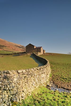 A Yorkshire Dales dry stone  wall leading to a stone barn Stock Photo - 2707136