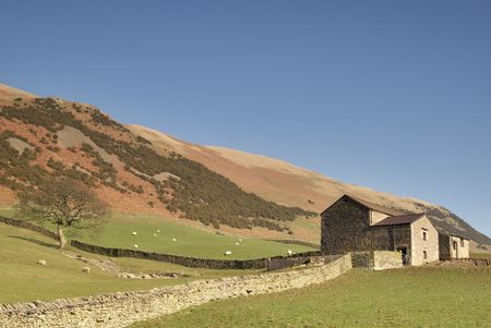 A Yorkshire Dales dry stone  wall leading to a stone barn Stock Photo - 2707135