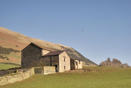 A Yorkshire Dales dry stone  wall leading to a stone barn Stock Photo - 2707134