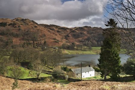 An Isolated white cottage by the side of Loughrigg Tarn in the English Lake District Stock Photo