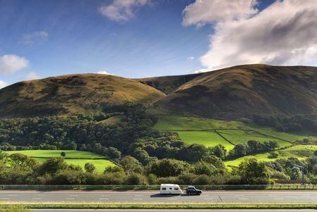 A samochód holujący przyczepie kempingowej na autostradzie M6 w Cumbrii. W Howgill wzgórza można obejrzeć w tle