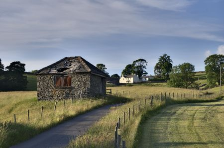 Small ruined barn on a rural road leading to a white farmhouse in the English Lake District Stock Photo - 3291553