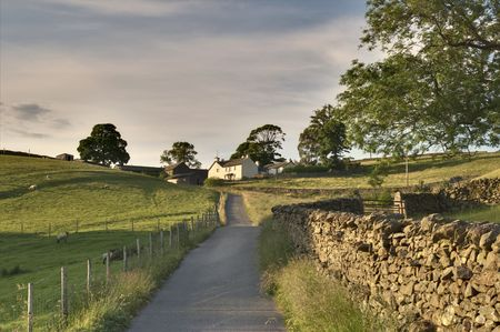 Rural road leading to a white farmhouse in the English Lake District Stock Photo - 3291559