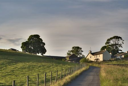 Rural road leading to a white farmhouse in the English Lake District 免版税图像