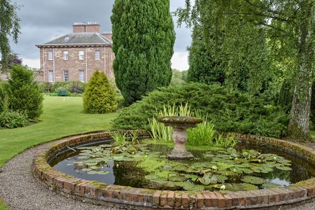 An ornamental pond in a country estate garden with a large  in the background Stock Photo