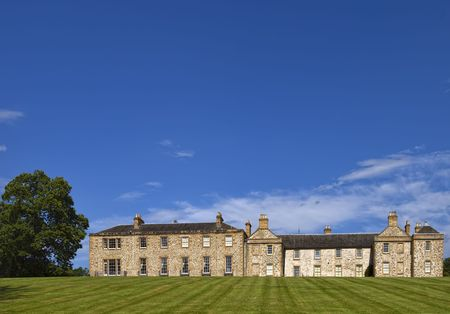 opulence: A large English country house with an elegant lawn under a blue sky
