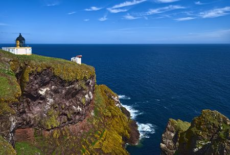 Pettico Wick is a beautiful inlet on Scotlands East Coast. The white lighthouse stands on the clifftop Stock Photo