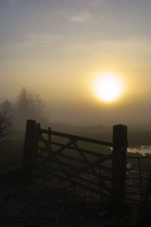 Silhouette of a wooden gate on a misty evening with the setting sun photo