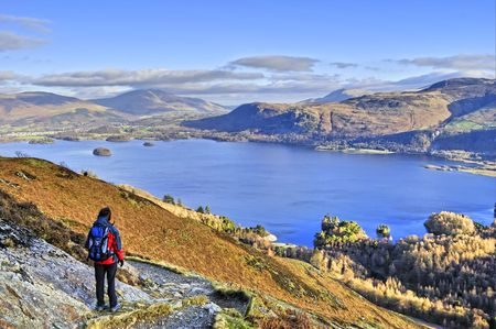 A Female hiker descending the path from Catbells with Derwent Water in the background photo