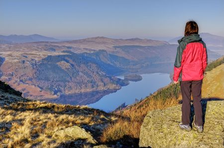 A Female hiker looking down on Thirlmere from the Wythburn path to Helvellyn Stock Photo