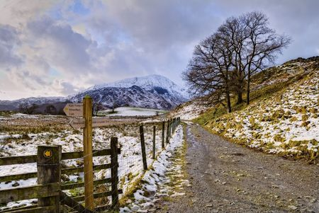 A snowy track and footpath sign in Little Langdale in the English Lake District. Wetherlam can be seen in the distance Stock Photo - 4341351