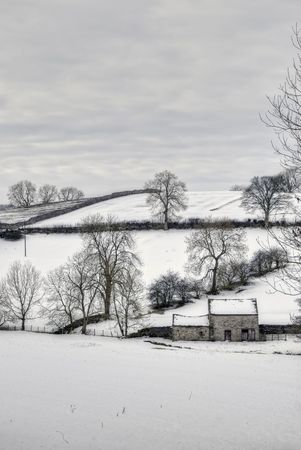 A landscape view of snow covered hills and fields on a cloudy day near Kirkby Stephen, Cumbria, England. Stock Photo