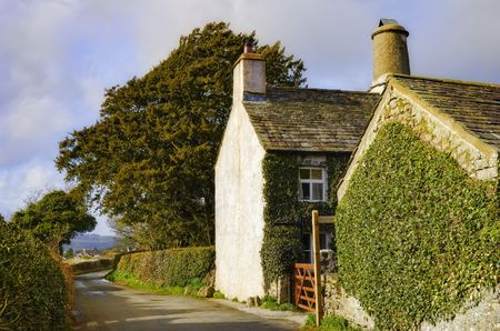 A view of the side of a quaint English cottage along the side of a narrow country road