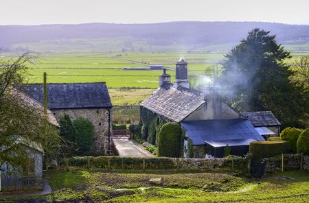 A view of a farmhouse and fields in Cumbria, Northern England Stock Photo - 4574440