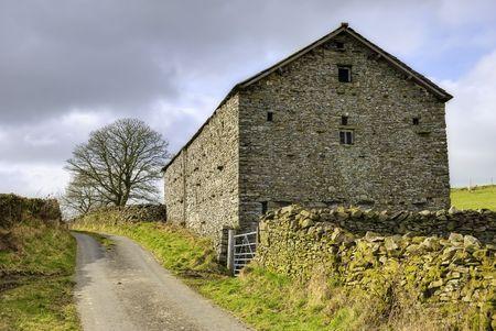 Exterior of stone barn in countryside next to lane, Cumbria, England. Stock Photo - 4574446