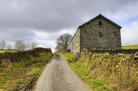 Scenic view of stone barn by countryside road, England. Stock Photo - 4574447