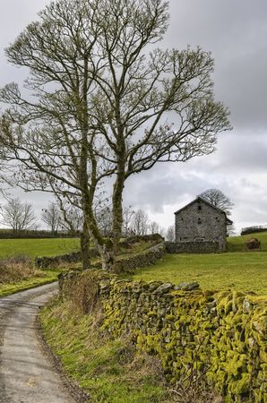 English country lane with stone barn building in background. Stock Photo - 4574448