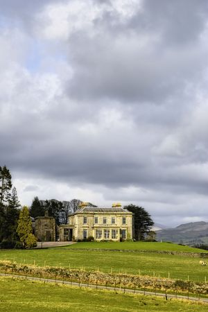 English country estate home against a dark cloudy sky and landscape.