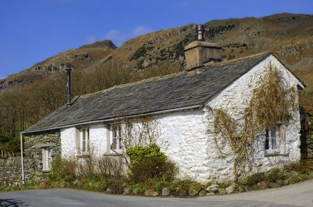 Exter of traditional whitewashed cottage in countryside with mountains in background, England Stock Photo - 4604331