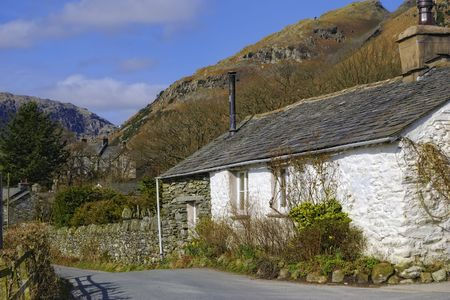 langdale: White cottage in countryside with mountainous background, Little Langdale village, Lake District, Cumbria, England