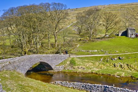 wharfedale: Scenic view of stone packhorse bridge over river Wharf with Yockenthwaite village in background, Wharfedale Valley, Yorkshire Dales, England.
