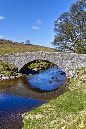 old packhorse bridge: Scenic view of stone packhorse bridge over river Wharfe, Wharfedale Valley, Yorkshire, England. Stock Photo