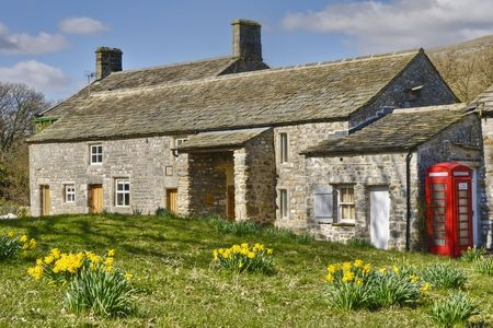 Exterior of stone cottage in countryside with red telephone box, Arncliffe, Yorkshire Dales National park, England.