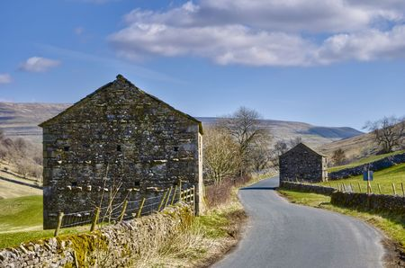 wharfedale: Exterior of two stone barns by countryside road, Wharfedale, Yorkshire Dales National Park, England.