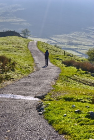Rear view of female hiker walking on pathway in Lake District National Park, Cumbria, England. Stock Photo - 4930815