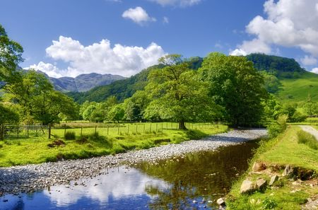 Widok rzeki Derwent przechodzącej przez bujne, zielone w pobliżu wsi Rosthwaite w Anglii.