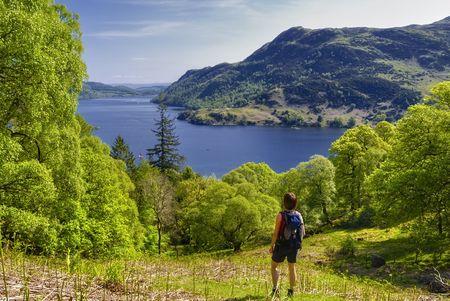 Kobieta turysta patrząc na Ullswater, Park Narodowy Lake District, Cumbria, Anglia.