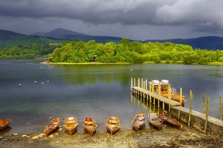 Scenic view of boats moored by wooden pier on Derwent Water, Lake District National Park, Cumbria, England.