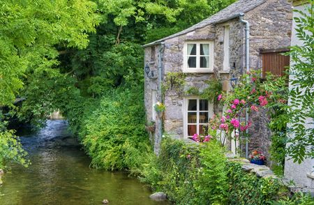 An old, quaint English cottage on the bank of a small river in Cartmel, England. Stock Photo