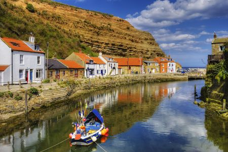 Scenic view of clouds reflecting on ocean with fishing boat in foreground, Staithes harbor, North Yorkshire, England 免版税图像