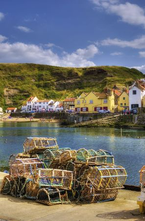 Scenic view of Staithes harbor and waterfront with lobster pots in foreground, North Yorkshire, England Stock Photo - 5625081
