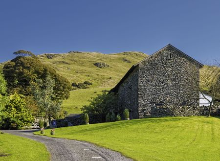 Scenic view of stone barn conversion in countryside with hills in background, Cumbria, England.