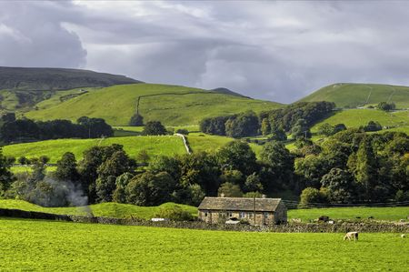 dales: Scenic view of farm in countryside, Yorkshire Dales National Park, England.