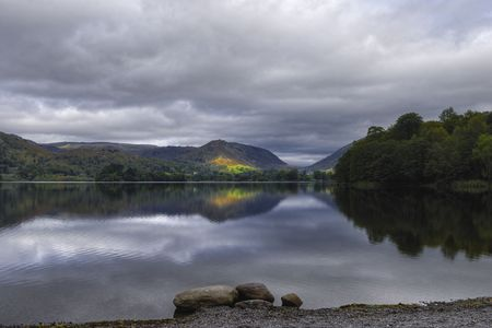 Scenic view of forested countryside reflecting on Grasmere Lake under cloudscape, Lake District National Park, Cumbria, England Stock Photo - 6006434
