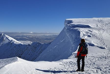 Rear view of female mountaineer on snowy summit of Helvellyn mountains in Winter, Lake District National Park, Cumbria, England. photo