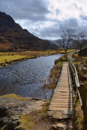 Scenic view of Watendlath Beck or river with wooden walkway and mountains in background, Lake District National Park, Cumbria, England. Stock Photo - 6923062