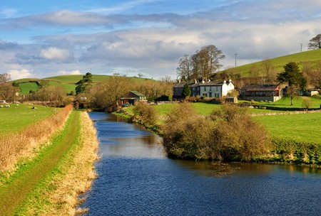 Scenic view of Lancaster Canal receding past rural homes in countryside, Farleton, Cumbria, England. Stock Photo - 7029268